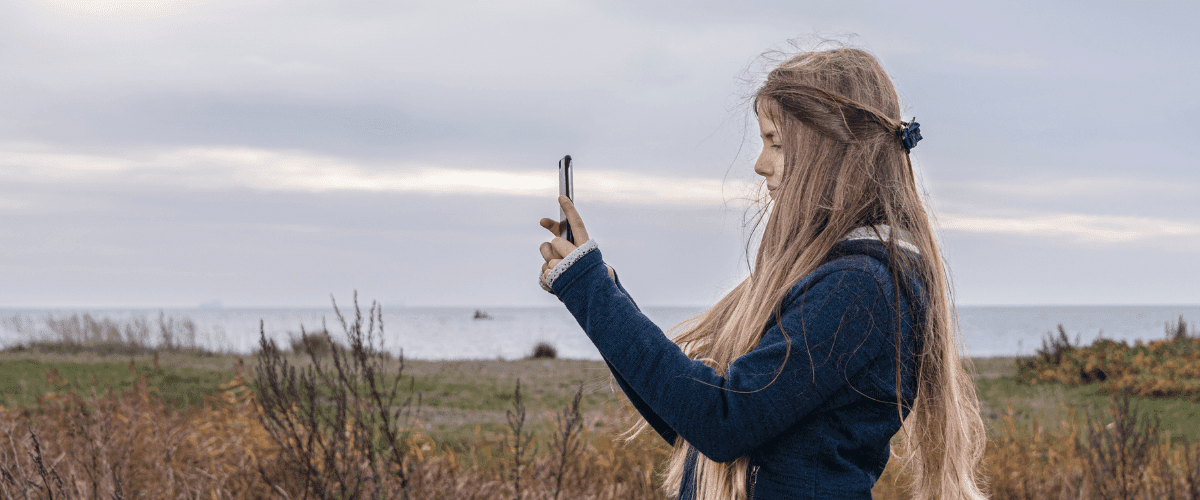 A young teenager with long blonde hair and wearing a blue sweater is standing in the grass near the shore of Lake Superior and is taking photographs with a smart phone she is holding in her hands.