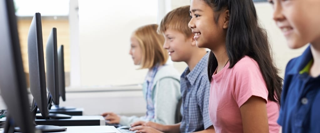 4 children, 3 in a blue shirts and one in a pink shirt are in a classroom sitting in a row next to one another, each looking at a computer screen.