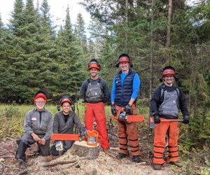 4 students and 1 instructor standing outside wearing safety equipment for chainsaw safety class